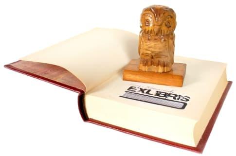 Pieczątka ex libris na książce, sowa jako uchwyt stempla.